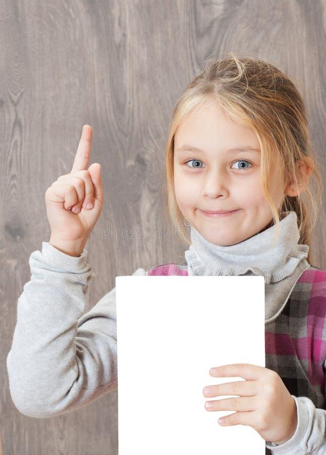 Liten flicka som rymmer ett ark av vitbok arkivfoto