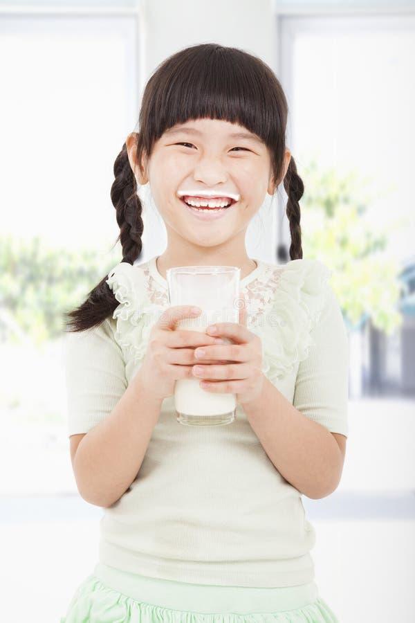 liten flicka som rymmer ett exponeringsglas av, mjölkar arkivbild