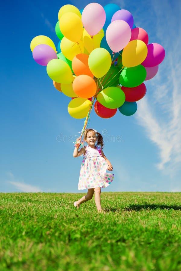 Liten flicka som rymmer färgrika ballonger. Barn som spelar på en gräsplan royaltyfri fotografi