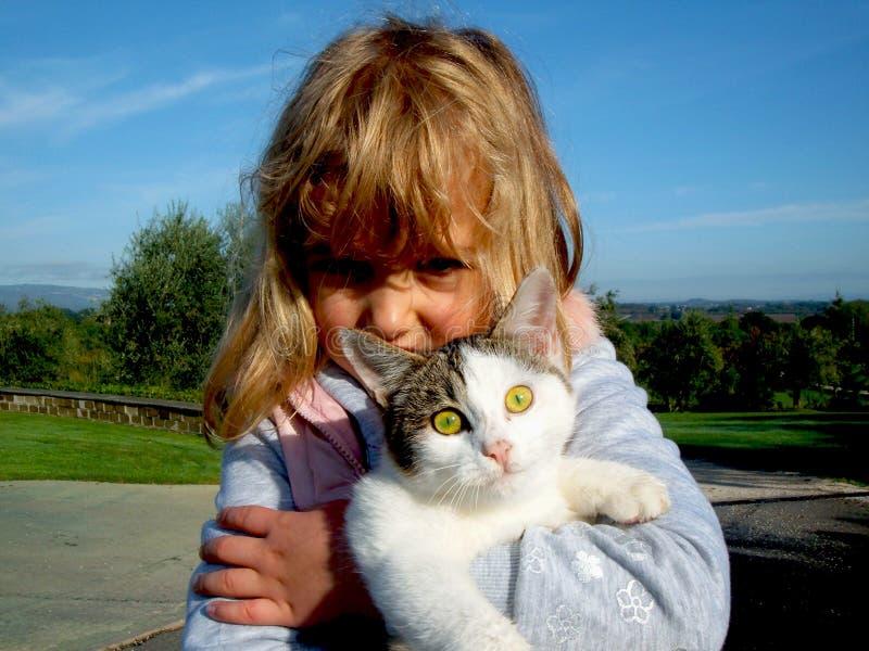 Liten flicka som rymmer katten royaltyfri fotografi