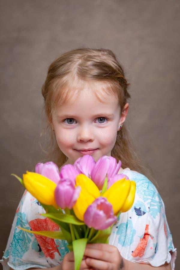 Liten flicka som rymmer tulpan arkivbild
