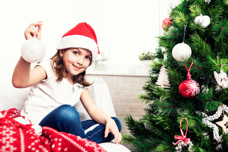 Liten flicka som sätter christmassträdprydnader royaltyfria bilder