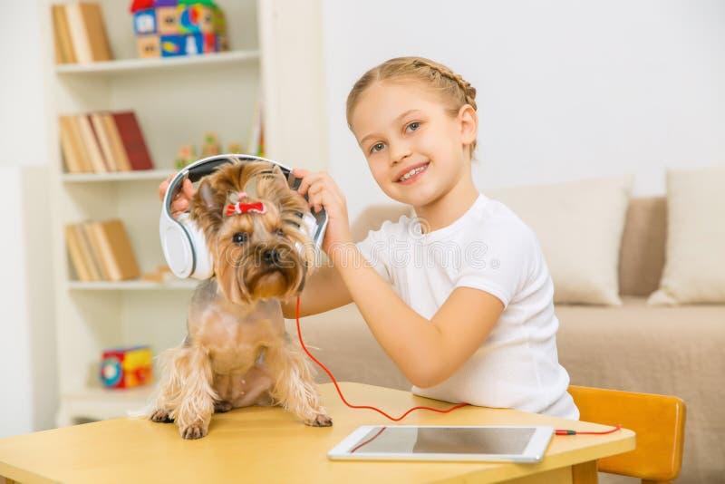 Liten flicka som sätter hörlurar på hunden royaltyfria foton