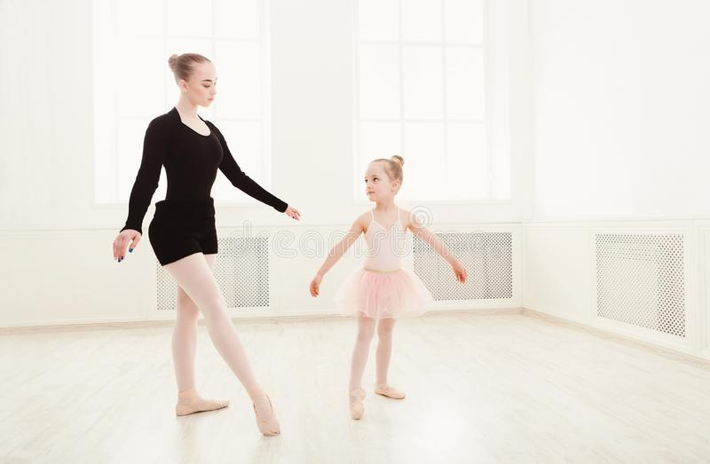 Liten flicka som ser den yrkesmässiga balettdansören arkivfoto