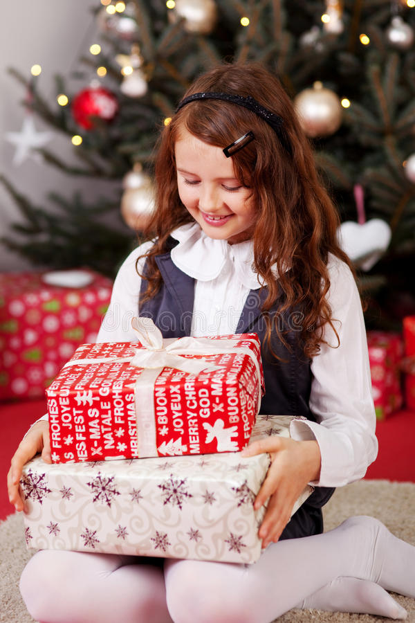 Liten flicka som ser hennes julgåvor royaltyfri bild