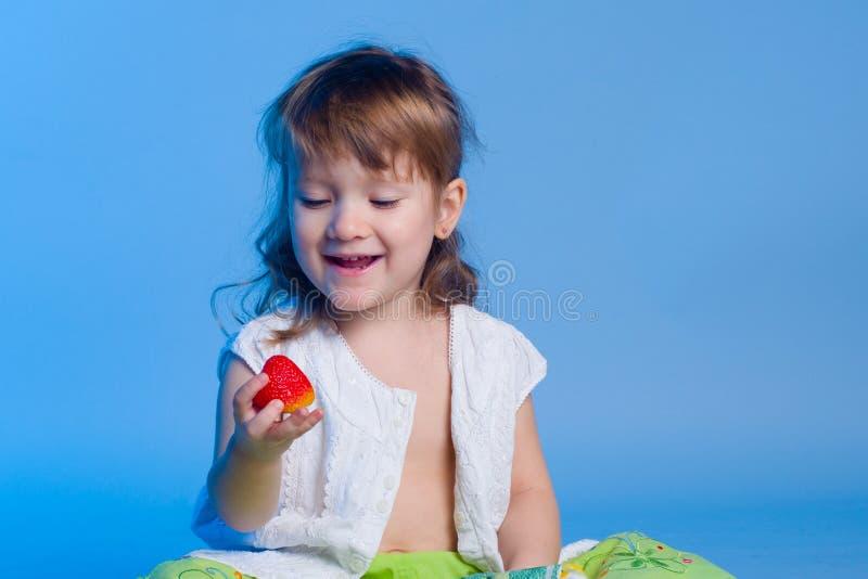 Liten flicka som ser jordgubben royaltyfria bilder