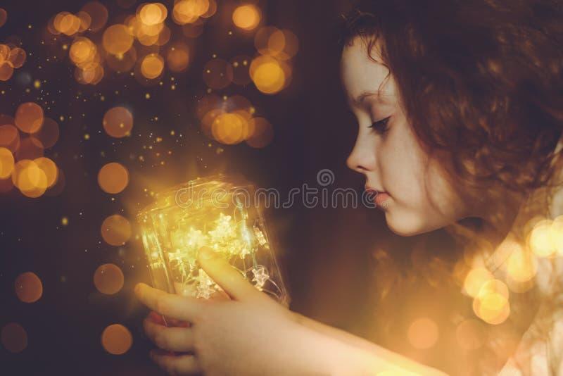 Liten flicka som ser på den magiska jullampan royaltyfria foton
