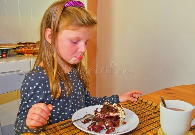 Liten flicka som ser på hennes födelsedagkaka Liten flicka som firar hennes sex födelsedag Lilla flickan äter kakan royaltyfria foton