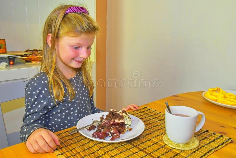 Liten flicka som ser på hennes födelsedagkaka Liten flicka som firar hennes sex födelsedag Lilla flickan äter kakan arkivfoton