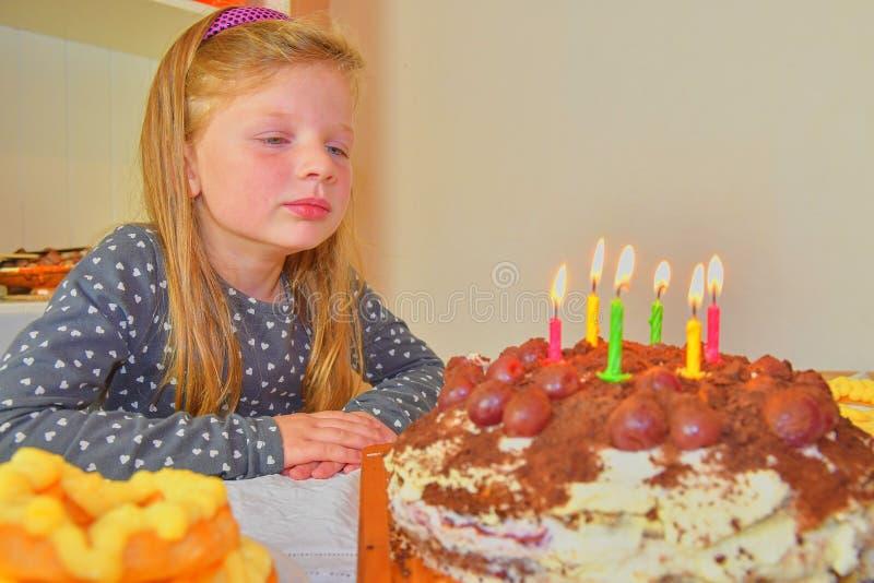 Liten flicka som ser på hennes födelsedagkaka Liten flicka som firar hennes sex födelsedag Födelsedagkaka och liten flicka royaltyfri bild