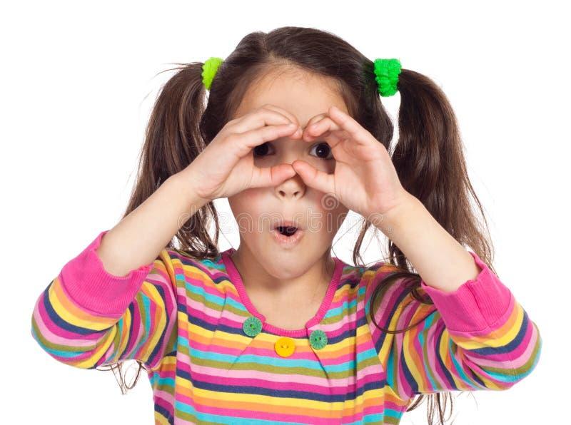 Liten flicka som ser till och med imaginärt binokulärt arkivfoto