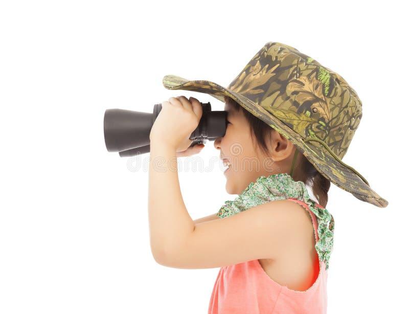 Liten flicka som ser till och med kikare Isolerat på vit arkivbild