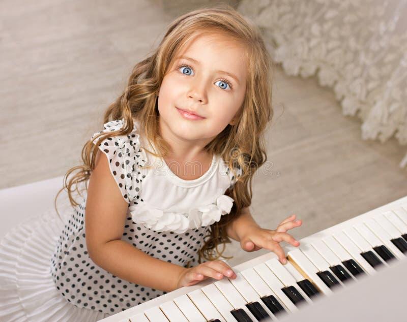 Liten flicka som sitter nära pianot arkivbilder