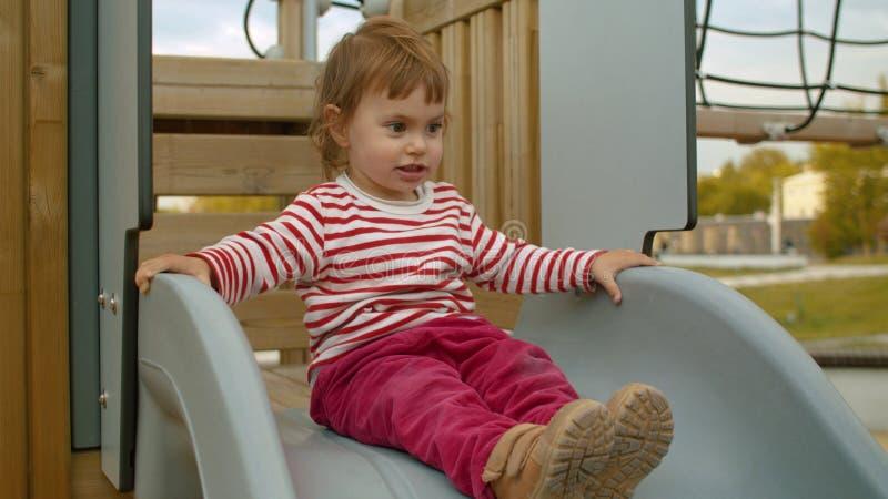 Liten flicka som sitter på en överkant av en glidbana arkivbild