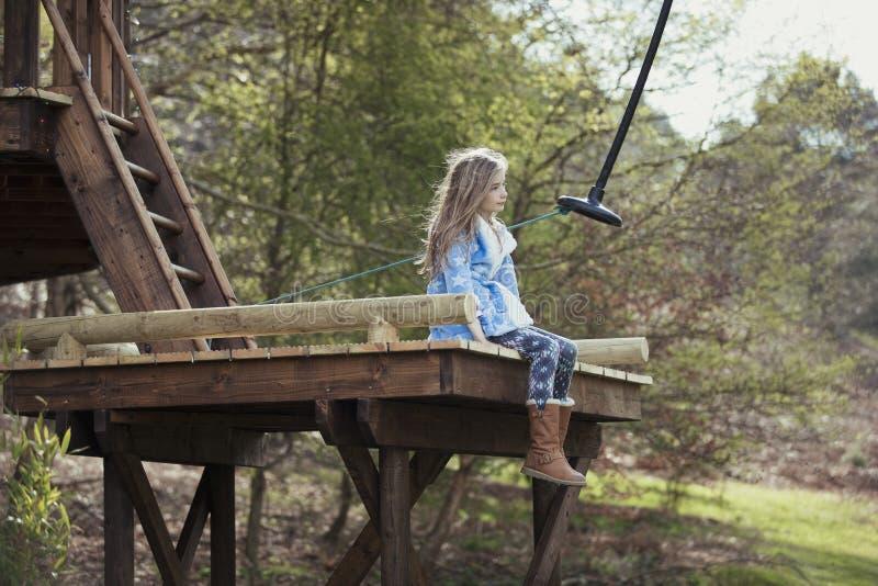 Liten flicka som sitter på en gungaplattform royaltyfri bild