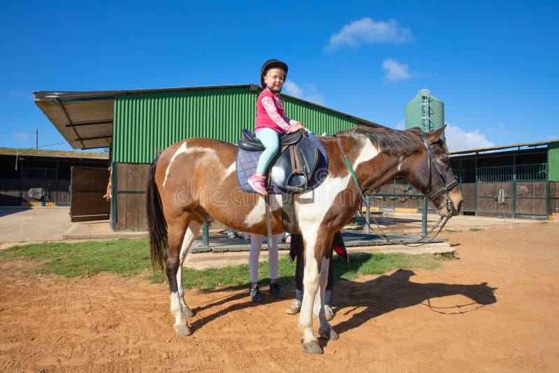 Liten flicka som sitter på en häst i en rida mitt som ser och royaltyfri foto
