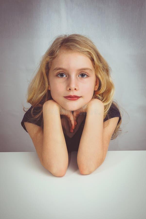 Liten flicka som sitter på en tabell och ser till mig med förälskelse royaltyfria foton