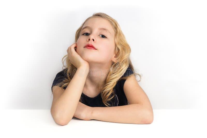 Liten flicka som sitter på en tabell och ser till mig med kuriositet fotografering för bildbyråer