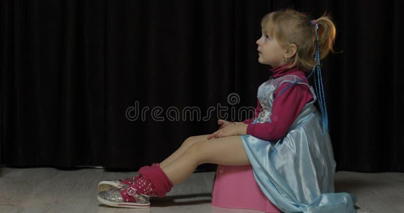 Liten flicka som sitter p? pottan och den h?llande ?gonen p? TV:N royaltyfria bilder