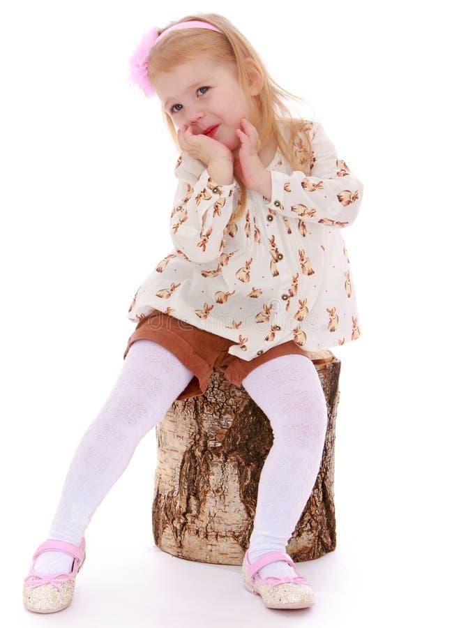 Liten flicka som sitts ner på en stubbe royaltyfria foton