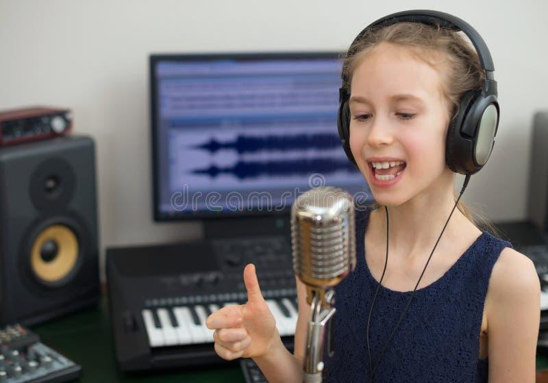 Liten flicka som sjunger en sång fotografering för bildbyråer