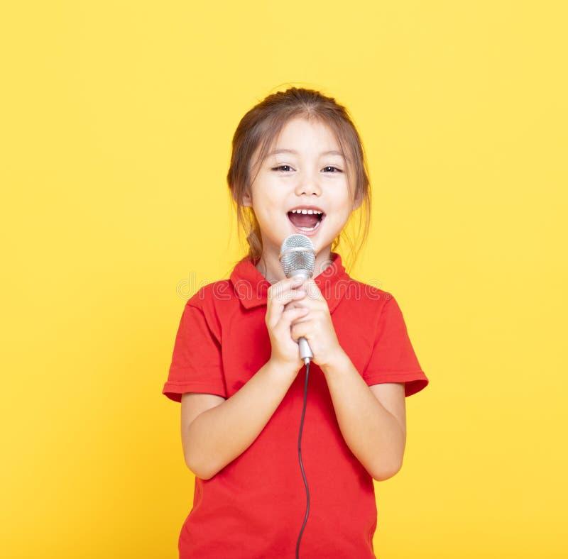 liten flicka som sjunger på gul bakgrund arkivbild