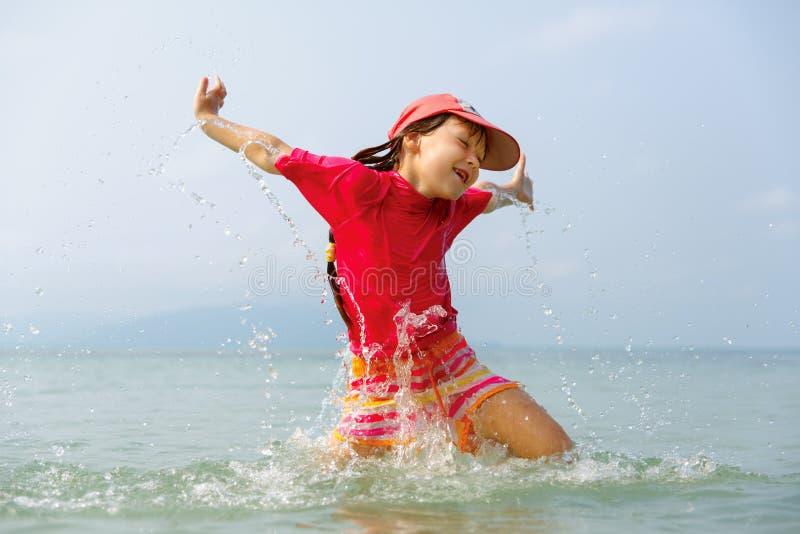 Liten flicka som skrattar och gråter i sprejen av vågor på havet royaltyfri foto