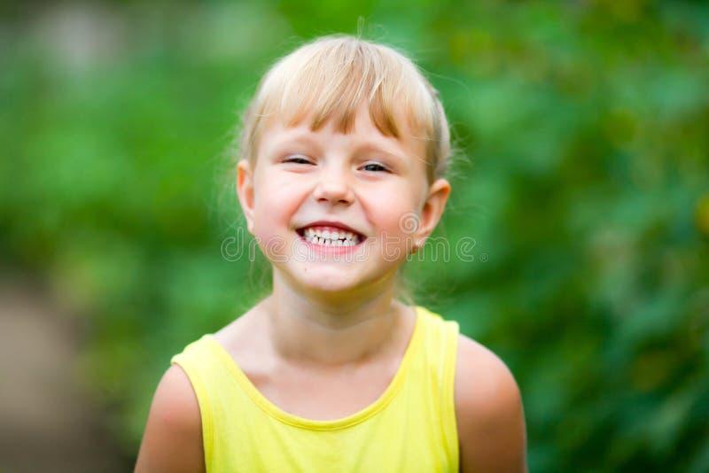 Liten flicka som skrattar och visar hennes tänder arkivbild