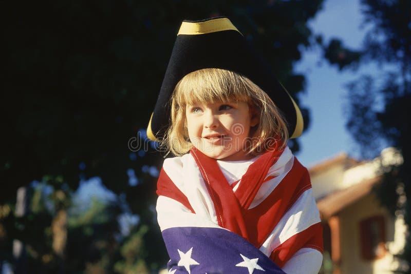 Liten flicka som slås in i amerikanska flaggan, royaltyfri foto