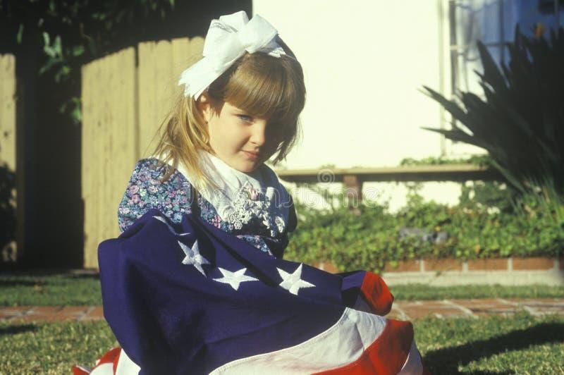 Liten flicka som slås in i amerikanska flaggan, Förenta staterna arkivbilder
