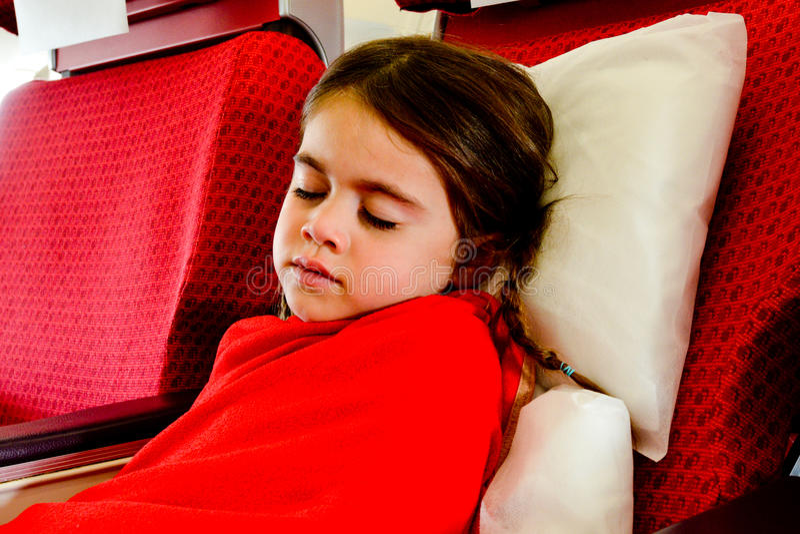 Liten flicka som sover i en nivå royaltyfri foto