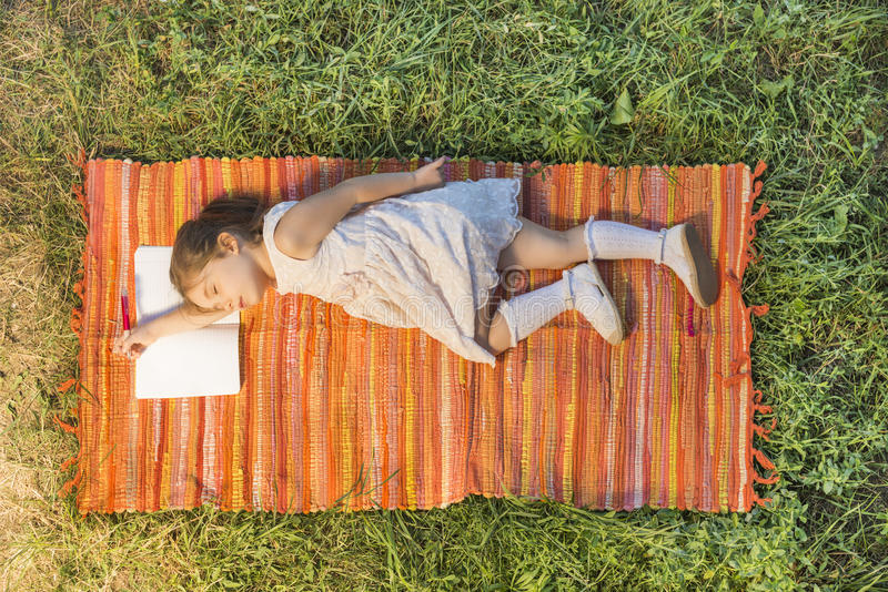 Liten flicka som sover på den öppnade anteckningsboken som ner ligger på picknickfilten royaltyfria bilder