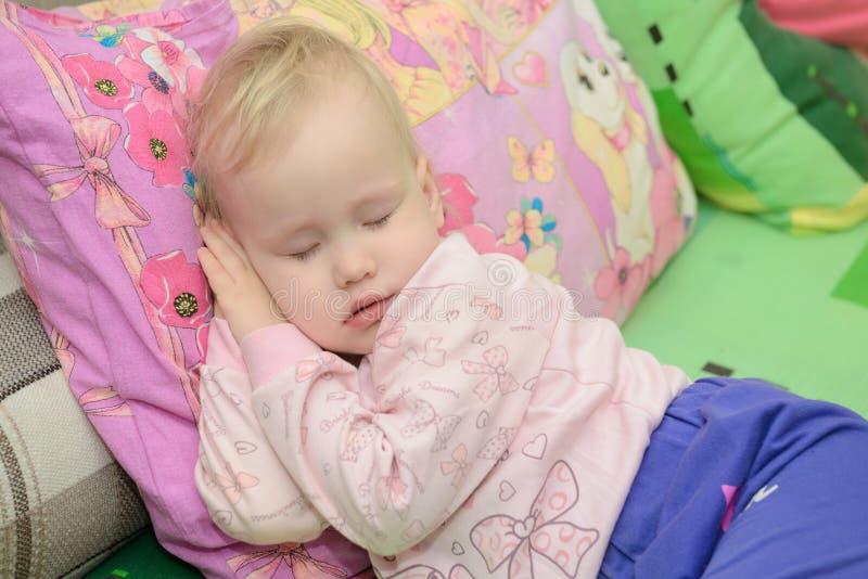 Liten flicka som sover på kudden royaltyfria foton