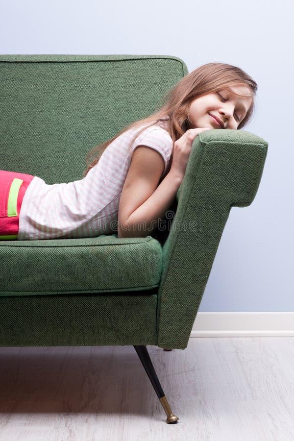 Liten flicka som sover slappt på en grön soffa arkivfoto