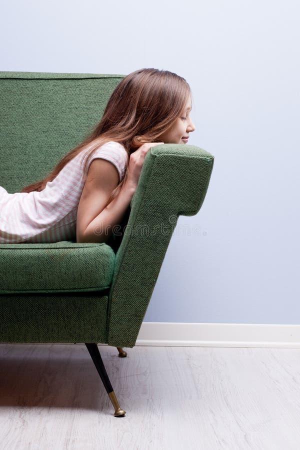 Liten flicka som sover slappt på en grön soffa arkivbild