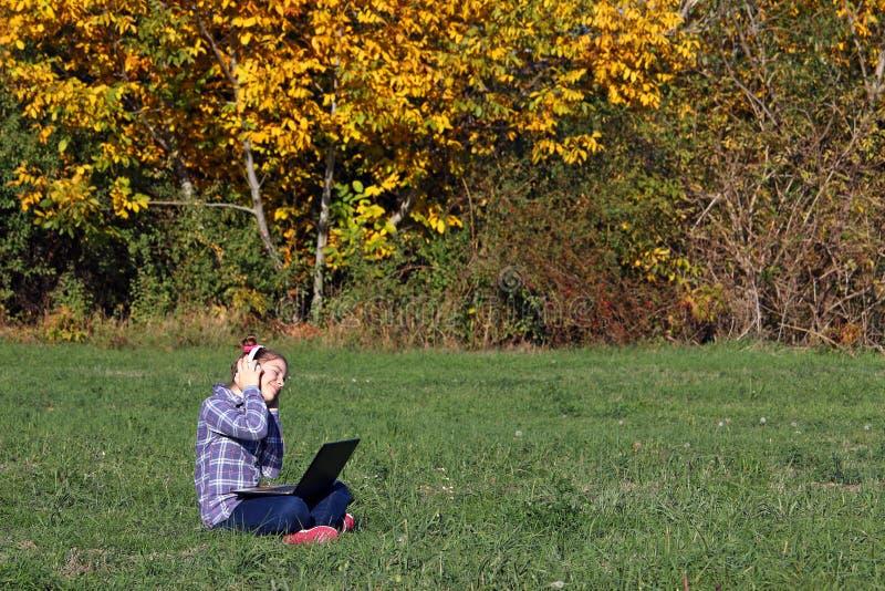 Liten flicka som spelar bärbara datorn och lyssnande musik på headphon royaltyfri fotografi