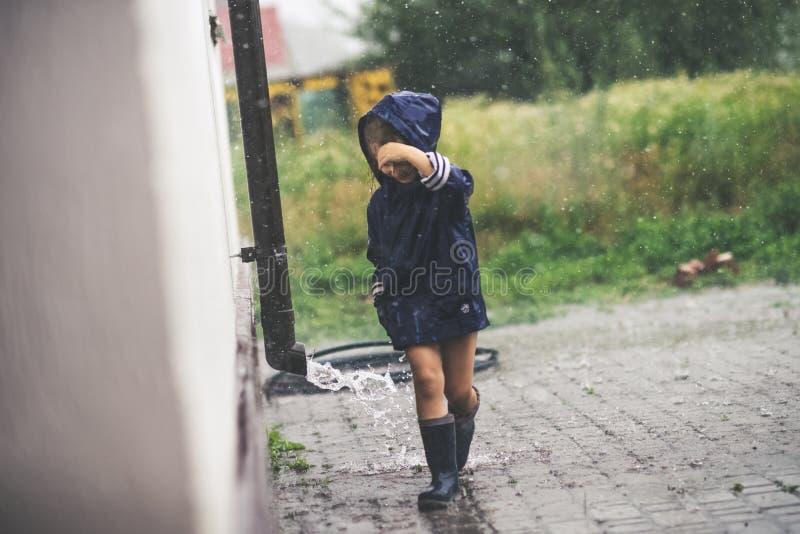 Liten flicka som spelar den ensamma yttersidan i dåligt väder royaltyfri bild
