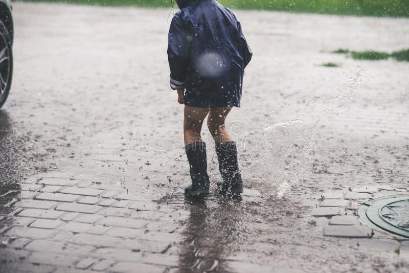 Liten flicka som spelar den ensamma yttersidan i dåligt väder arkivbild