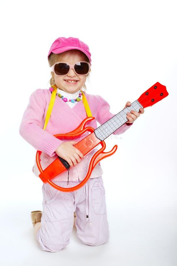 Liten flicka som spelar den hardcore elektriska gitarren arkivbild
