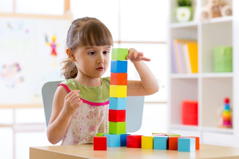 Liten flicka som spelar färgrika träsnitt arkivfoto