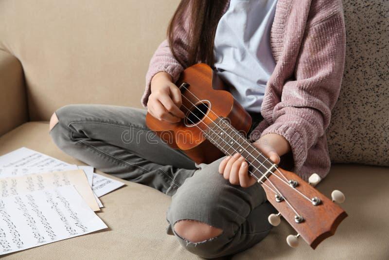 Liten flicka som spelar gitarren på soffan arkivbild