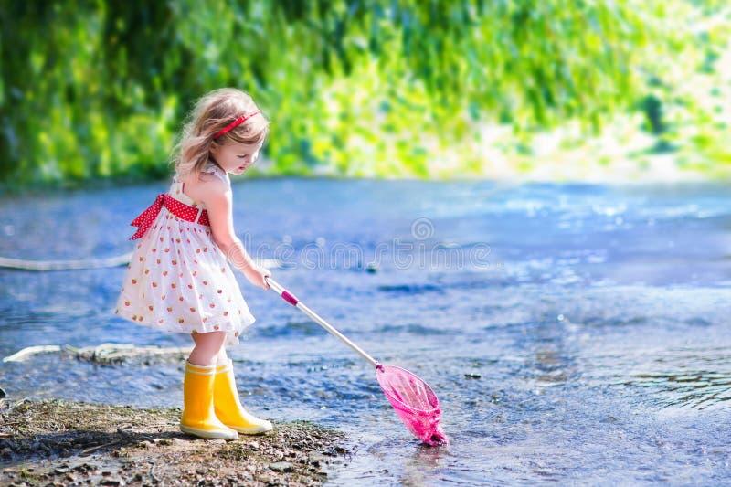 Liten flicka som spelar i en flod arkivfoton