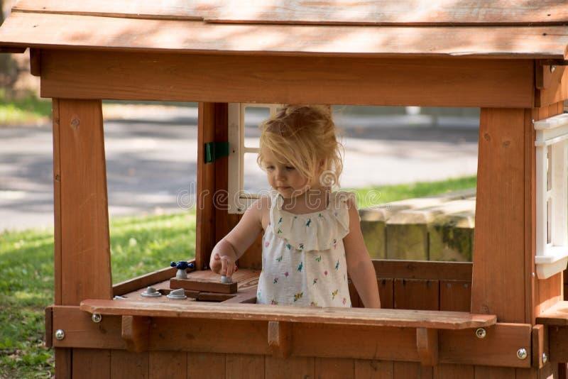 Liten flicka som spelar i hennes lekstuga utanför arkivfoton