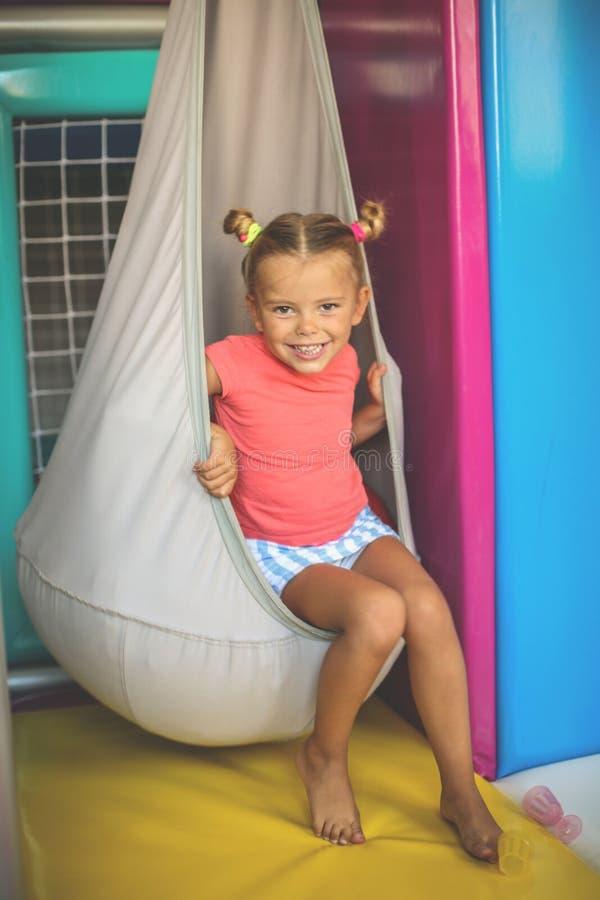 Liten flicka som spelar i lekplats Caucasian flickasammanträde på th arkivfoton