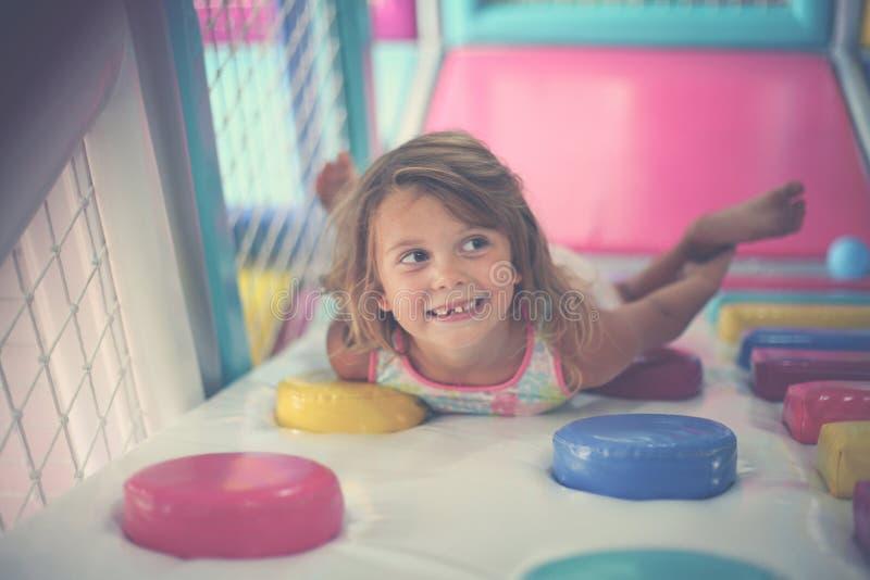 Liten flicka som spelar i lekplats Caucasian flicka som ligger i playr royaltyfri fotografi