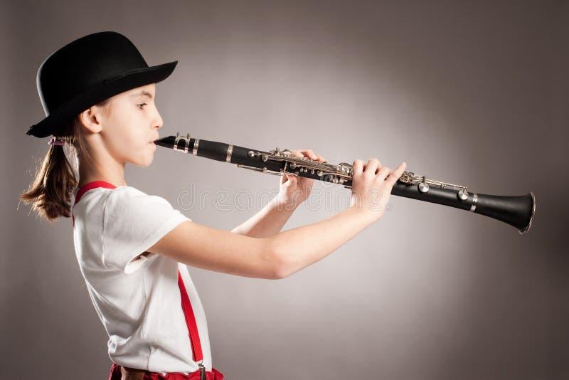 Liten flicka som spelar klarinetten arkivfoton