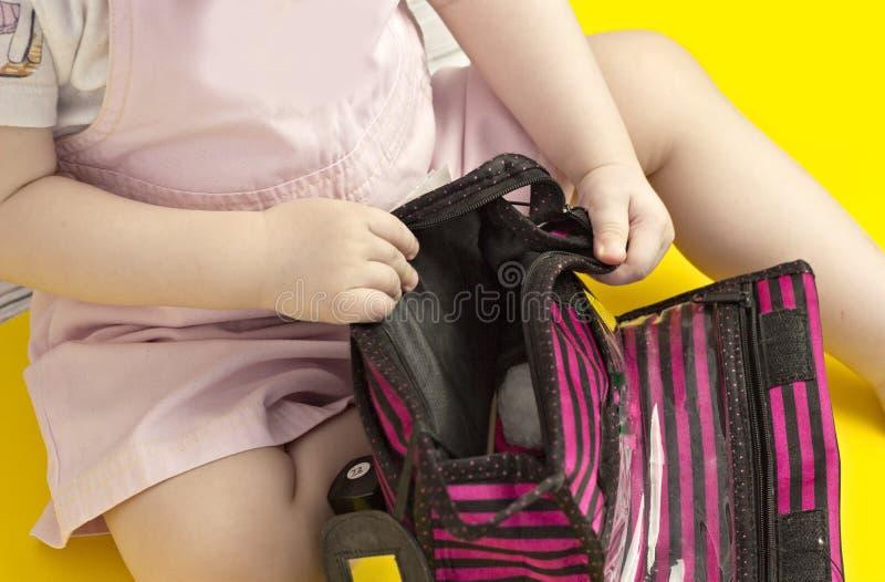 Liten flicka som spelar med den kosmetiska påsen, gula bakgrundsskönhetsmedel royaltyfri foto