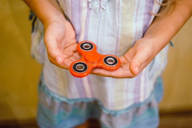 Liten flicka som spelar med den röda rastlös människaspinnareleksaken royaltyfria bilder