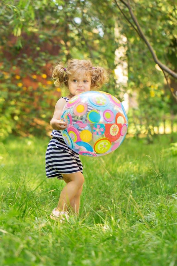 Liten flicka som spelar med den stora bollen på grön gräsmatta royaltyfri foto