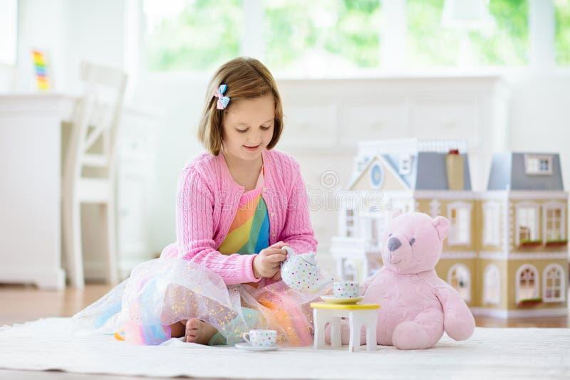 Liten flicka som spelar med dockhuset Unge med leksaker royaltyfri foto
